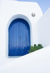 Closed blue door in a greek house