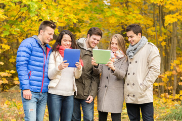 group of smiling friends with tablets in park