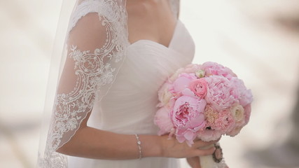 Bride standing with gorgeous bridal bouquet of pink peonies