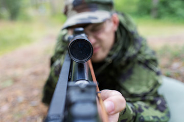 close up of soldier or hunter with gun in forest