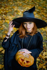 Halloween, girl in witch dress with pumpkin