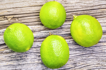 Four citrus lime fruits on wooden boards