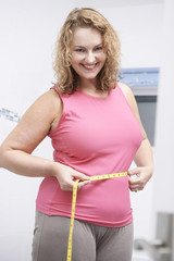 Happy Plus Size Woman Measuring Waist In Bathroom