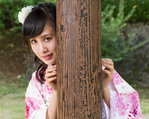 Asian woman in kimono behind wooden pillar