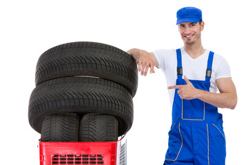 Cheerful mechanic pointing in new tires