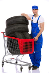 Young mechanic with  tires in shopping cart