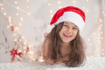 A cute smiling girl in a Santa hat
