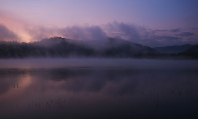 Fog at dawn over the lake in the Bieszczady Mountains