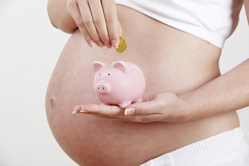 Close Up Of Pregnant Woman Putting Coin Into Piggy Bank