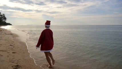 Woman on the Beach in Santa Hat. Christmas Vacation. Slow Motion