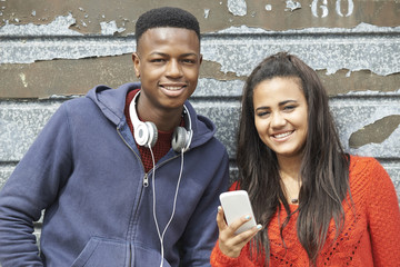 Teenager Couple Sharing Text Message On Mobile Phone