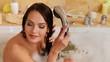 Young woman washing hair in  bubble  bath.