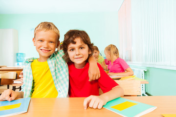 Two boys hugging and sitting together in classroom