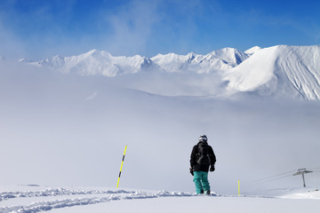 Snowboarder on snowy slope with new fallen snow