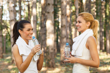 Beautiful fitness woman drinking water from plastic bottles