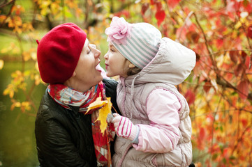 girl and mother are hiding behind a tree in the autumn park