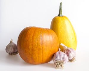 Two pumpkins, orange and yellow, and garlic