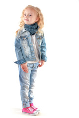Girl in denim suit and a scarf around her neck looking back over
