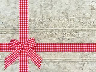 Holzhintergrund mit rotkariertem Geschenkband und Schleife