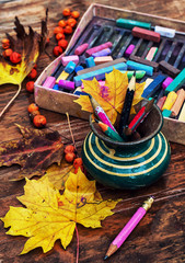 vase with colored pencils and autumn leaves