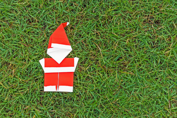 Origami santa claus on grass