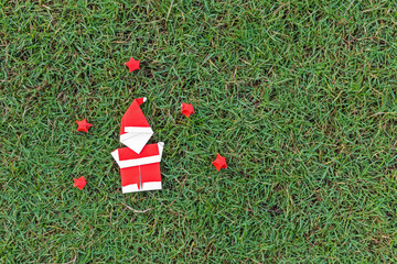 Origami santa claus and stars on grass