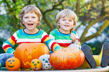 Two little kid boys making jack-o-lantern for halloween in autum