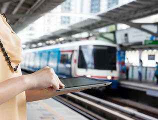 Woman using digital tablet at skytrain station