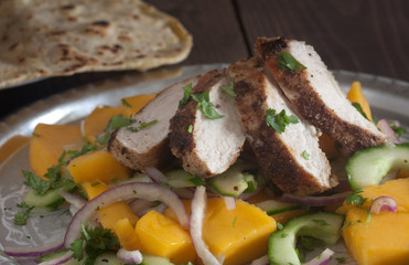 Grilled chicken breast with fresh mango salad and naan bread