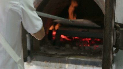 HD Chef putting pizza in a wood fire brick oven