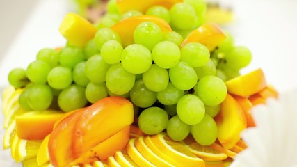 Plate with fresh fruits grapes lemon persimmon