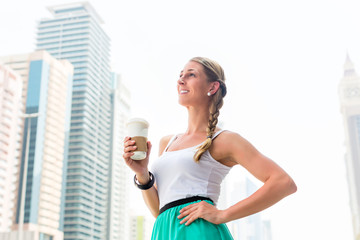 Woman enjoying coffee to go in metropolitan city
