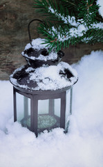 Christmas card with fir branch and a lantern on a wooden backgro