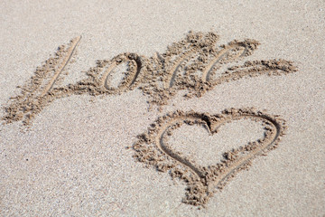 Love written on the sand with a hearth drawing