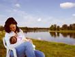 Brunette mum breastfeeding in the country