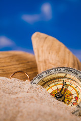 compass on sand and blue sky