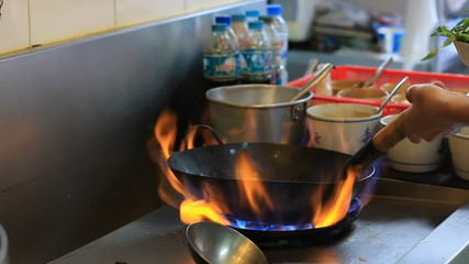 Saucepan on fire during cooking in kitchen