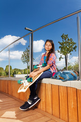 Smiling girl holding skateboard and sits in park