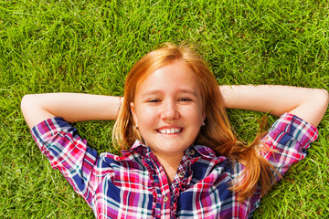 Girl with arms under her head lays on green grass