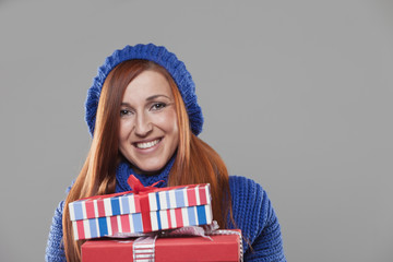 Smiling Woman Holding Stack of Christmas Presents