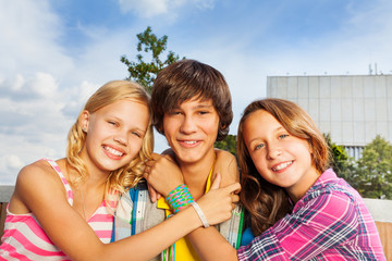Two girls embracing boy's neck and smile happily
