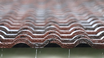 Falling Rain drop on brown brick roof