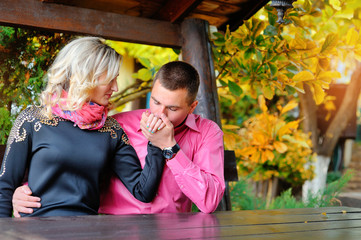 man and woman in love sitting on the bench and he kisses her han