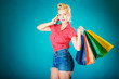 canvas print picture - Pinup girl with shopping bags calling on phone