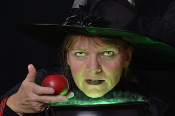 Hexe hält roten Apfel über Kessel mit grünem Dampf sehr nahe