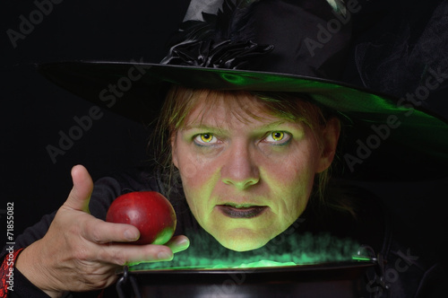 GamesAgeddon - Hexe hält roten Apfel über Kessel mit grünem Dampf ...