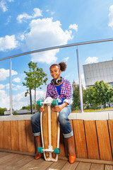 African girl holds skateboard and sitting on side