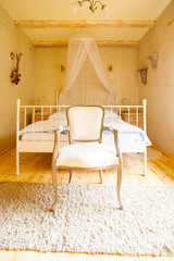Interior of bedroom. Canopy bed and retro chair.