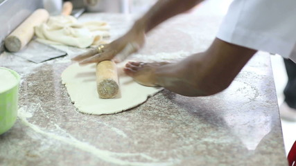 HD close up chef rolling dough of pizza in kitchen