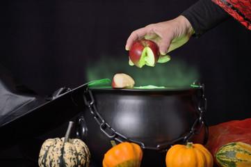 Hand hält roten Apfel in grünen Dampf über Hexenkessel